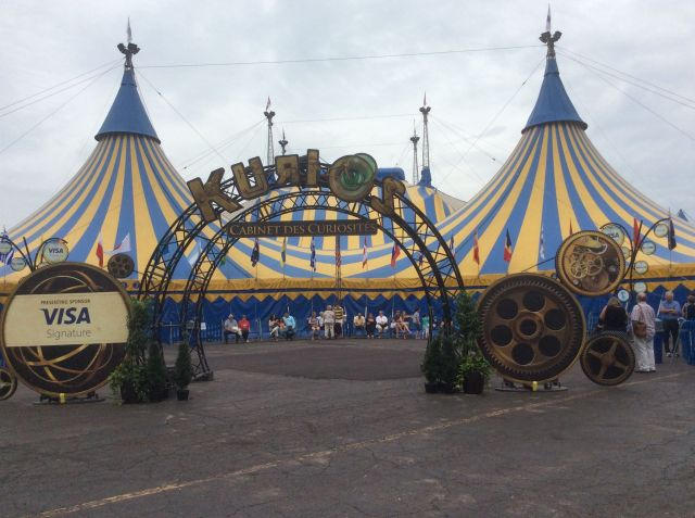 Cirque tent: large multi-post tent made of bold yellow and blue stripes with a decorative arc entrance